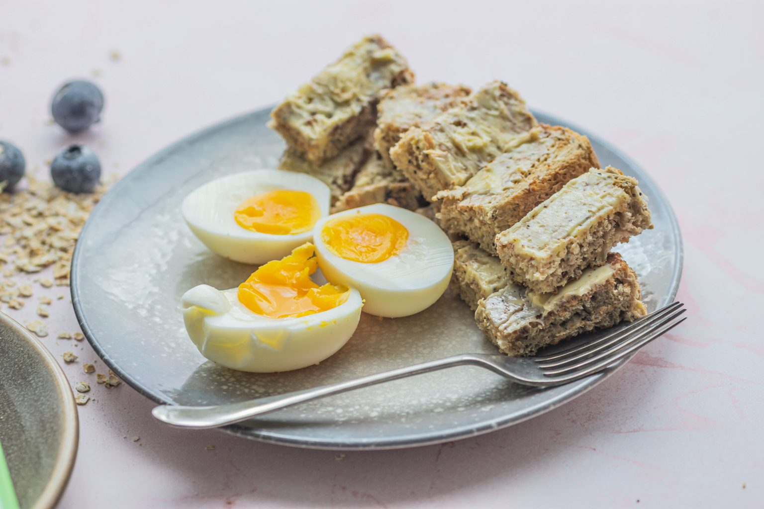 Three halves of a soft boiled egg with little wholemeal buttered toast soldiers and a small fork
