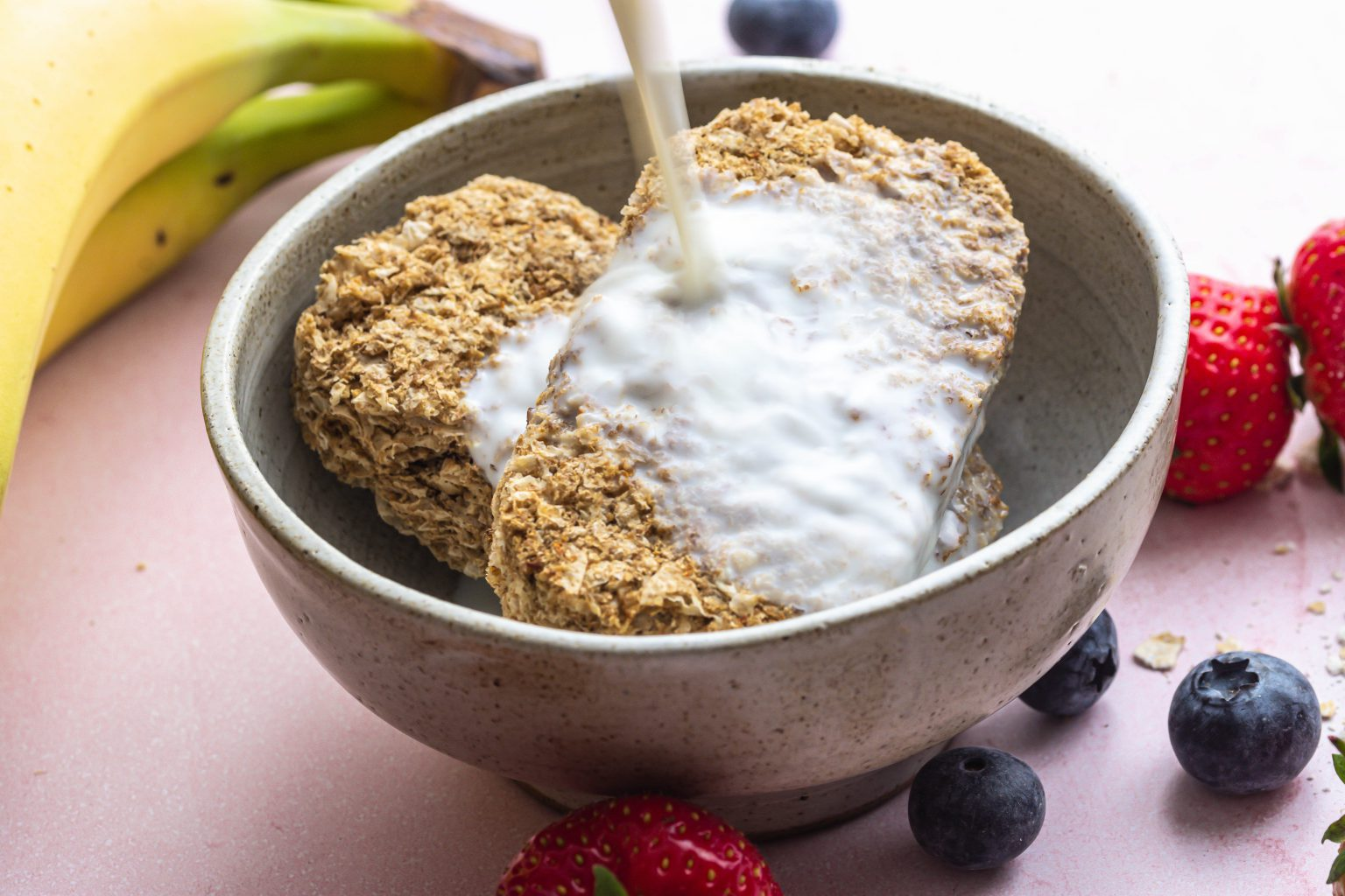 Milk being poured onto Weetabix in a bowl