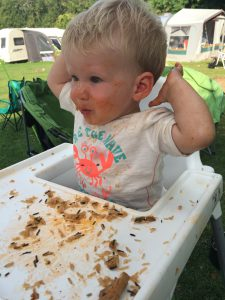 Toddler in a highchair on a campsite - food everywhere