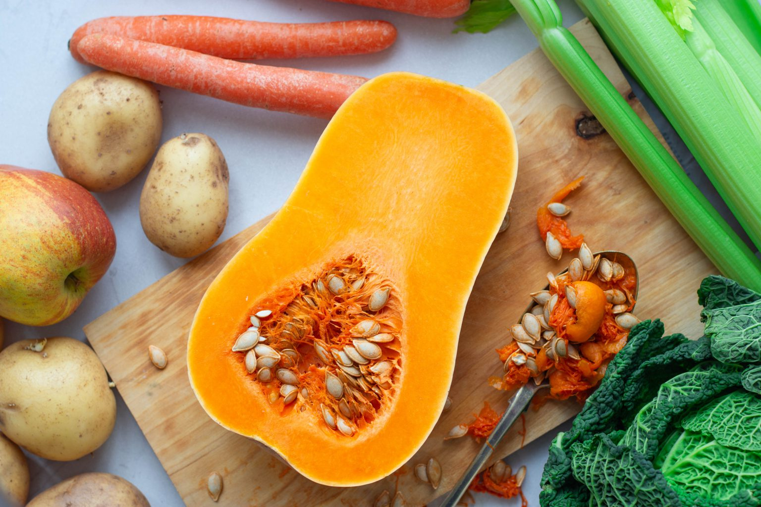 Butternut squash cut open with seed spilling out surrounded by apples, potatoes, carrots, celery & cabbage